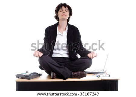 Business woman sitting on her desk doing yoga - stock photo