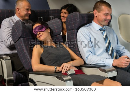Business woman sleep during night flight airplane cabin passengers - stock photo