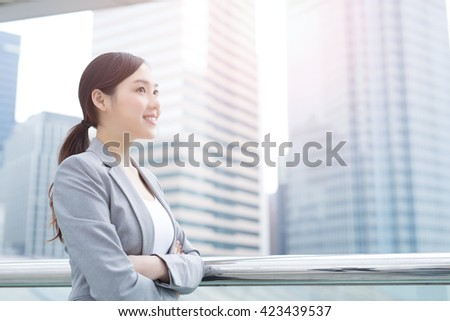business woman smile and look with office background, asian beauty, shot in Hong Kong - stock photo