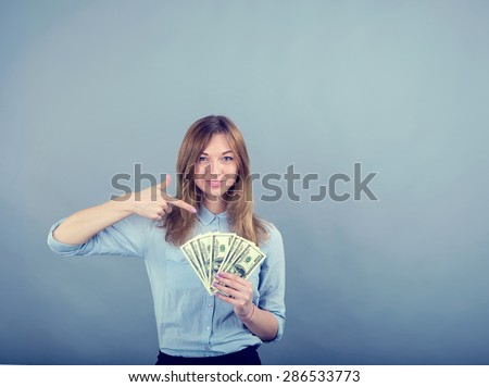 Business woman smiling and pointing finger to money on grey blue background. Woman pointing at USA notes. Young woman holds the money US dollars. Save for study. Girl student to receive a scholarship. - stock photo
