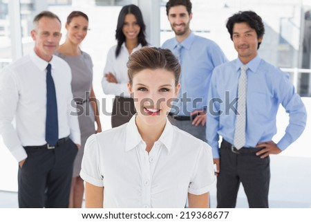 Business woman smiling at camera with co-workers behind her - stock photo