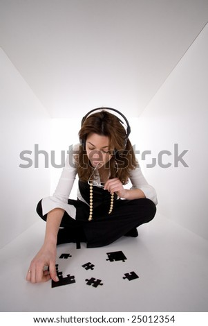 Business woman solving a puzzle problem in white cube space - stock photo