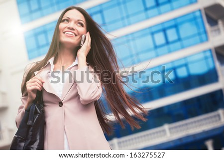 Business woman speaking cellphone on the street - stock photo