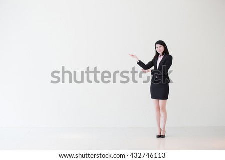 business woman stand and show something with white wall background, great for your design or text, asian - stock photo