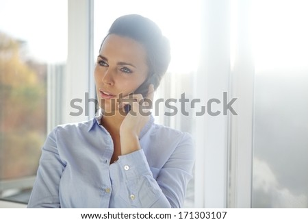 Business woman standing in a bright office while talking on her mobile phone looking away. Beautiful caucasian female model dressed in blue shirt. - stock photo
