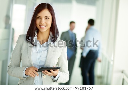 Business woman standing in foreground with a tablet in her hands, her co-workers discussing business matters in the background, tilt up - stock photo