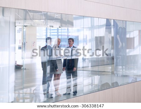 Business woman standing with her staff in background at modern office  - stock photo