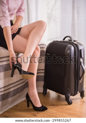 Business woman taking down her shoes while sitting on bed near suitcase at the hotel room. Close-up. - stock photo