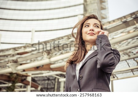 Business woman talking at phone - Asian woman with elegant dress and skyscraper in the background  - Business,technology,multiracial concepts - stock photo