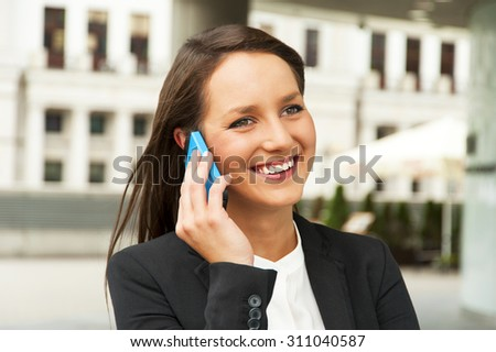 Business woman talking by smart phone against the glass wall in the city. - stock photo