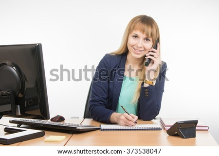 Business woman talking on the phone, writing in a notebook, and looked into the frame - stock photo