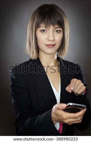 business woman texting on a mobile phone shot in the studio onm a gray background - stock photo