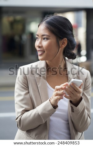 Business woman texting on her phone outdoors - stock photo