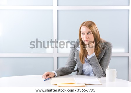 Business woman thinking in a modern office - stock photo