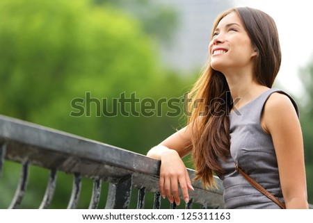 Business woman thinking in Central Park, New York City. Young female professional businesswoman thinking smiling happy outdoors. Mixed race Caucasian / Asian Chinese woman in her 20s. - stock photo