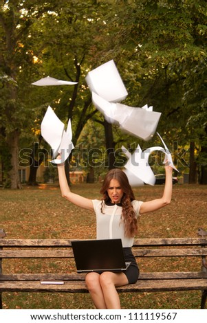 Business woman throwing paper in the air in park - stock photo