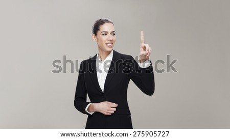 Business woman touching the screen with her finger on grey background - stock photo