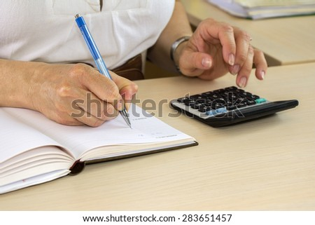 Business woman typing on calculator in the office - stock photo