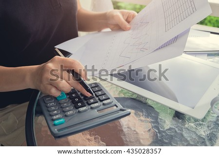 Business woman using a calculator to calculate the numbers on desk  - stock photo
