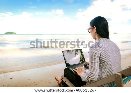 Business woman using a laptop beside the beach - stock photo