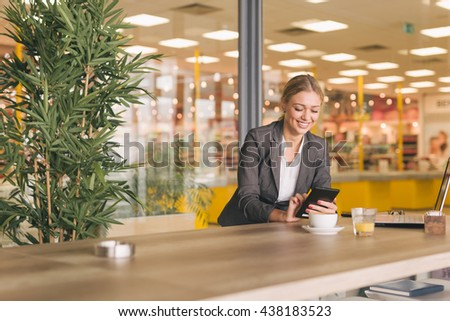 Business woman using her tablet in cafeteria - stock photo