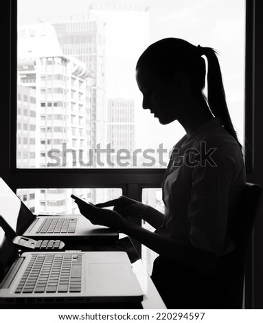 Business woman using mobile phone in the office - stock photo