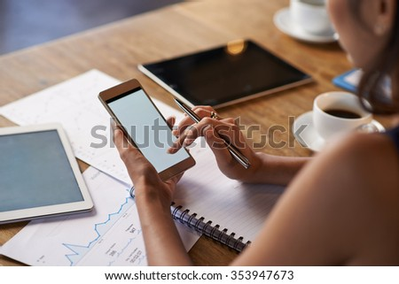 Business woman using smartphone when working with financial documents - stock photo
