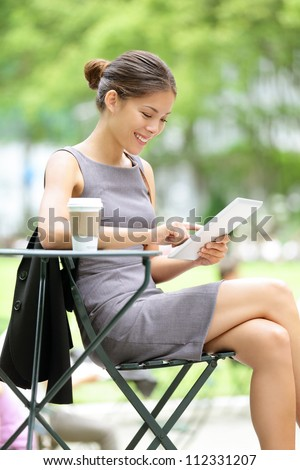 Business woman using tablet on lunch break in city park. Young professional businesswoman sitting at table at cafe. Photo from Bryant Park, New York City, USA. - stock photo