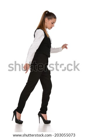 Business woman walking along a tightrope, isolated on a white background. - stock photo