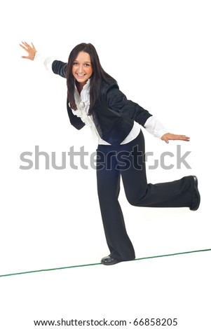 Business woman walking on a tight rope and trying to keep her balance isolated on white background - stock photo