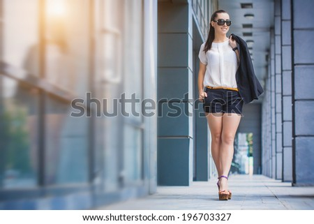 Business woman walking outside in city. office worker in downtown. - stock photo