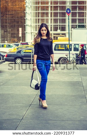 Business Woman Walking. Wearing black long sleeve sweater, blue pants, bracelets, hand carrying a leather bag, a pretty lady is walking on busy street, looking down, sad, thinking. - stock photo