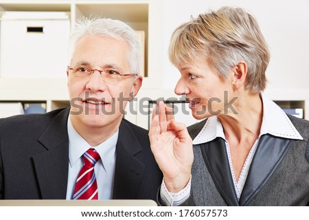 Business woman whispering a secret in a man's ear in the office - stock photo