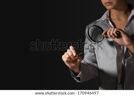 business woman with a magnifier and pencil, without a face - stock photo
