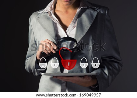 business woman with a magnifier safety checks on a Tablet PC - stock photo