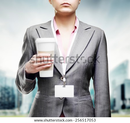 Business woman with a tumbler of coffee drinking and enjoying the aroma of invigorating coffee on a street on the way to office. Coffee break during working day. Downtown area in the background. - stock photo