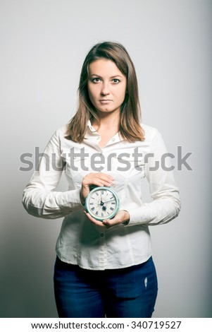 Business woman with an alarm clock in the hands of, office manager. studio photo on a gray background - stock photo