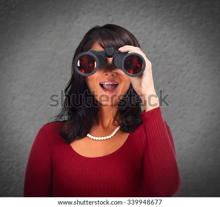 Business woman with binoculars over gray wall abstract background. - stock photo