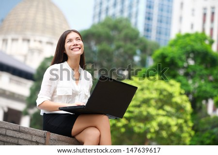 Business woman with computer laptop thinking looking up at copy space in business district, Central, Hong Kong. Young female professional businesswoman sitting relaxing. Asian Chinese Caucasian woman - stock photo
