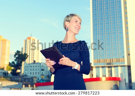 Business woman with digital tablet. European woman using tablet pc computer outdoor on a city street. Businesswoman working on digital tablet outdoor over building background and blue sky.  - stock photo