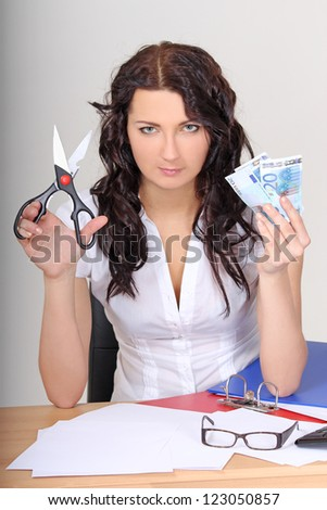 business woman with euro and scissors in office - stock photo