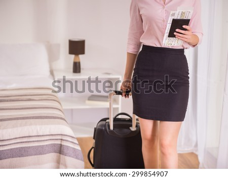Business woman with her documents and suitcase at the hotel room. Close-up. - stock photo