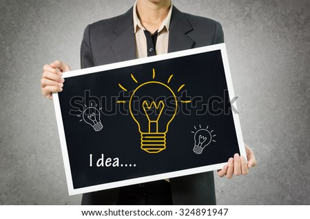 Business woman with idea light bulb icon in Black chalkboard on gray wall Background. - stock photo