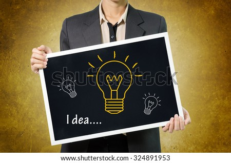 Business woman with idea light bulb icon in Black chalkboard on wall Background. - stock photo