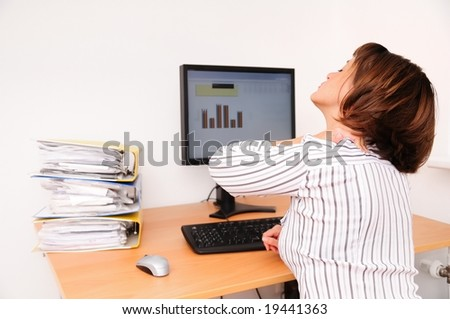 Business woman with neck pain sits on workplace with documents and monitor on table - stock photo