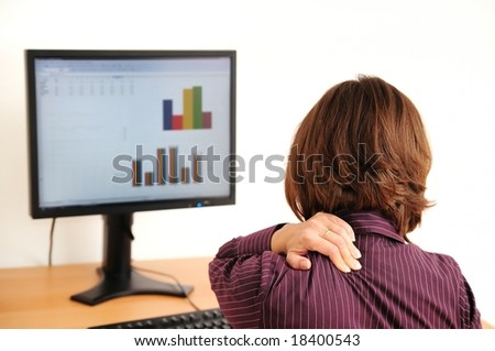 Business woman with neck pain sitting at computer - stock photo
