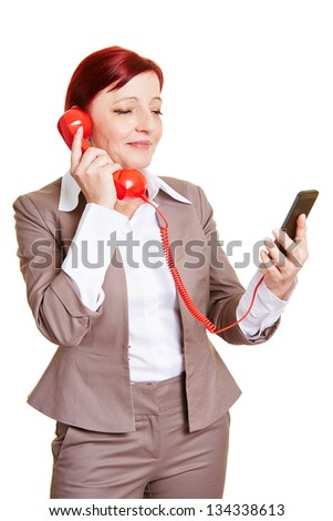 Business woman with smartphone and red phone receiver - stock photo