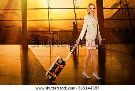 Business woman with suitcase in hall of airport - stock photo