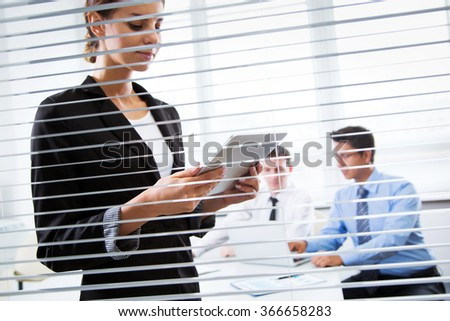 Business woman with tablet computer. View through blinds - stock photo