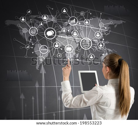 business woman with tablet touching media icons on virtual wall, back view  - stock photo